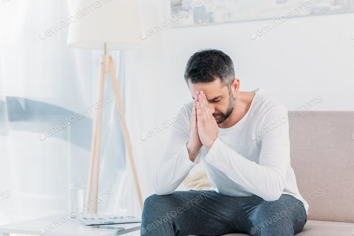 handsome bearded man with eyes closed doing please gesture and praying at home
