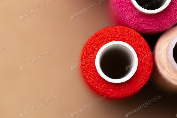 Many colored spools of threads as a background