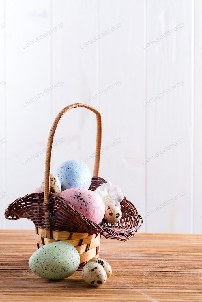 Festive Easter wicker basket with handmade painted chicken and quail eggs on a wooden table