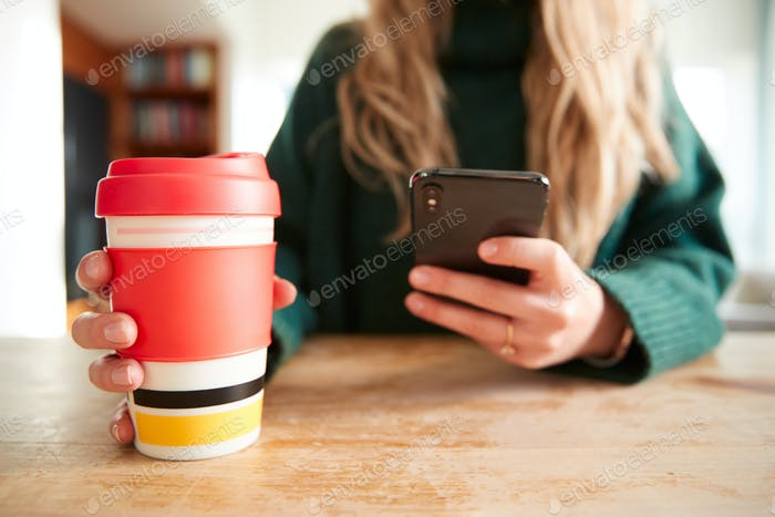Close Up Of Woman Using Mobile Phone With Reusable Takeaway Drink Cup Sitting At Table  In Cafe