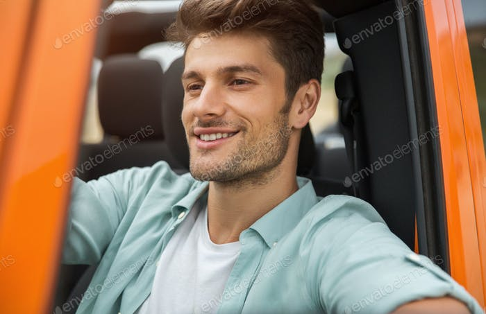 Handsome smiling man sitting on a front seat
