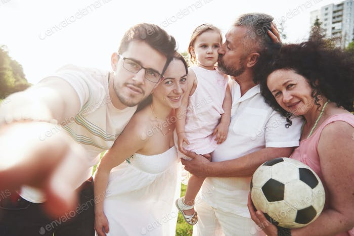 Cheerful active family having fun at countryside in summer day