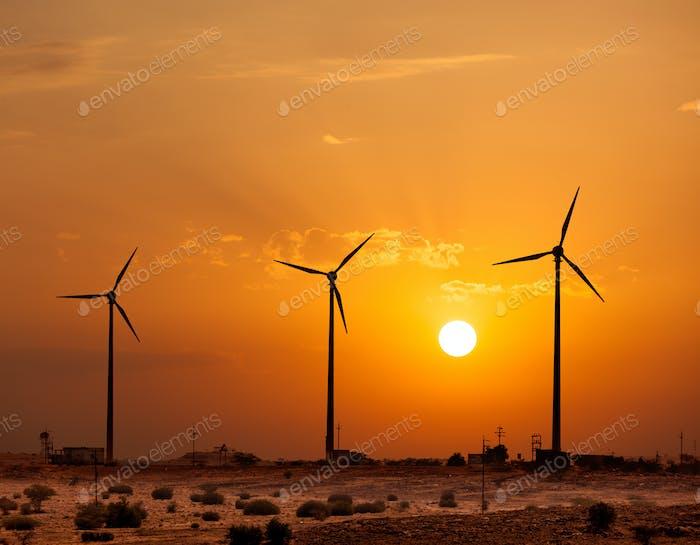 Wind generator turbines sihouettes on sunset