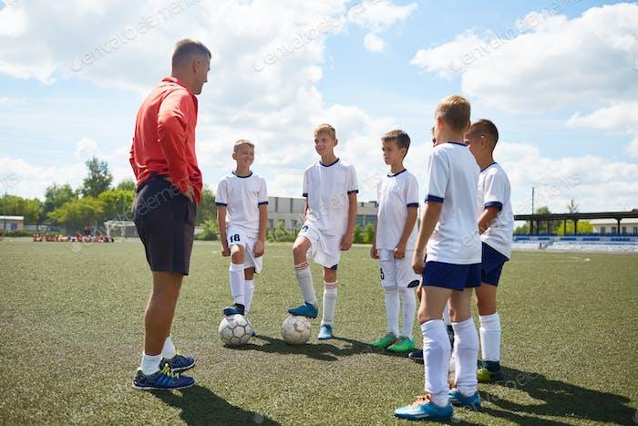 Junior Football Team Listening to Coach