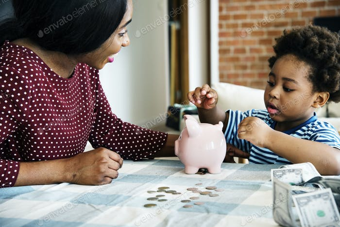 Mom and son saving money to piggy bank