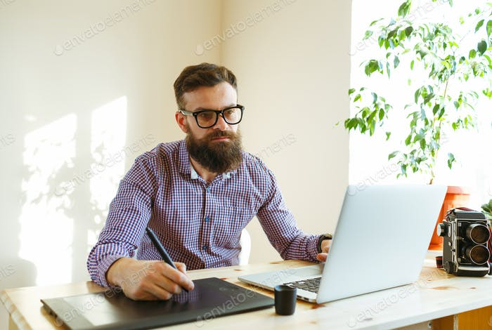 Beard young man working from home