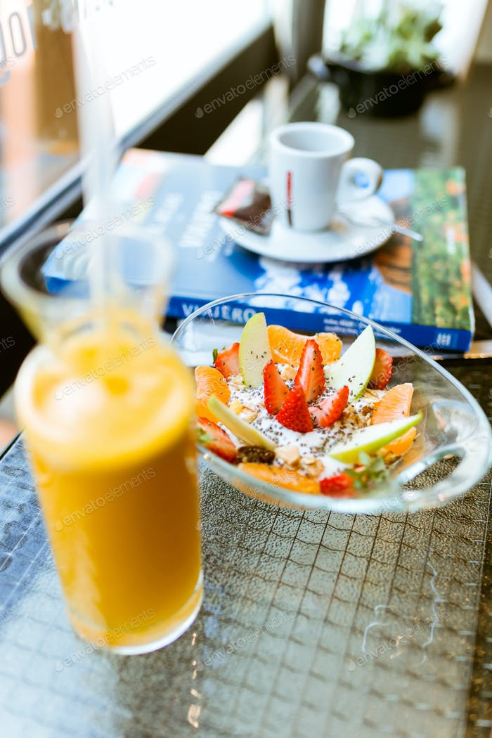 Healthy yogurt with fruits and orange juice in a restaurant.