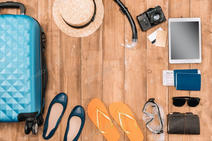 Travel background with tourist's outfit and closed luggage, shoes, digital devices and passports on