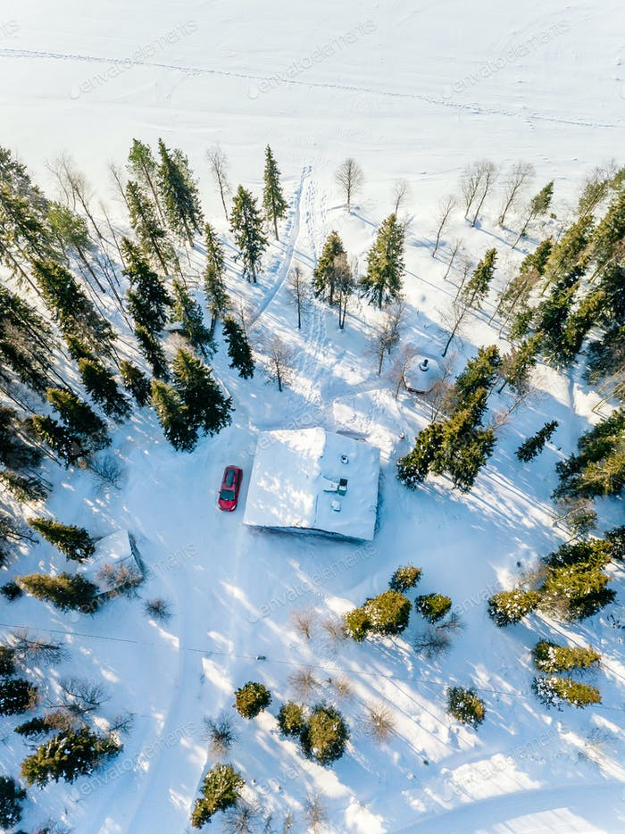 Aerial view of wooden log cabin in snow  winter forest by the lake in rural Finland