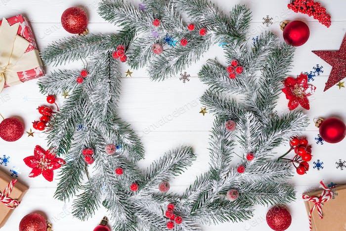 Weihnachts-Grußkarte mit Dekor und Tannenzweig auf weißem Holzhintergrund. Draufsicht mit