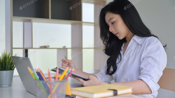 Asian woman working in office and looked at the documents in hand with laptop and office supplies.