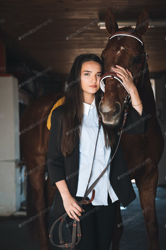 Pretty young woman standing in barn hugging her horse