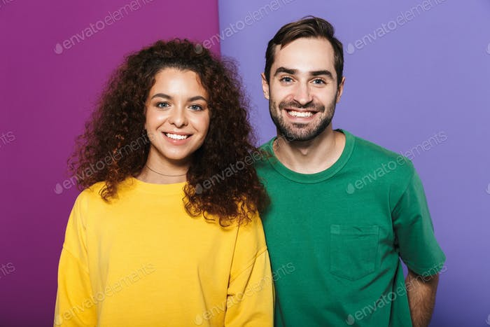 Portrait of young caucasian couple man and woman in colorful clothing smiling together at camera