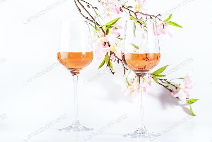 Rose wine glass with bottle on the white table and pink flowers