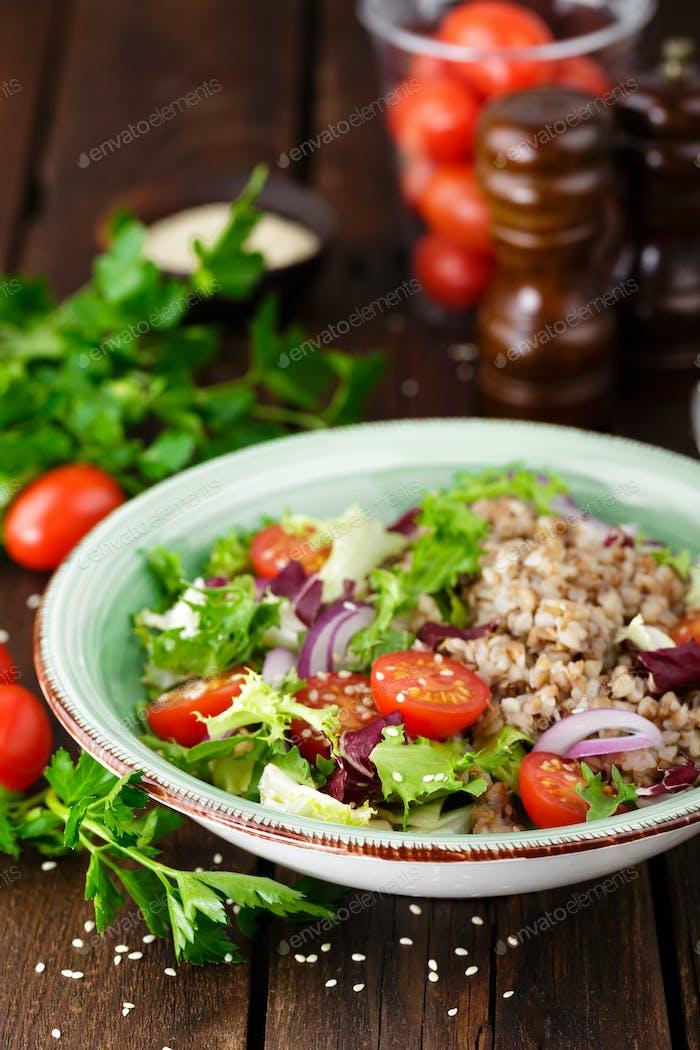 Frischer Gemüsesalat mit Salat, Zwiebeln, Tomaten und Buchweizenbrei. Gesundes veganes Essen