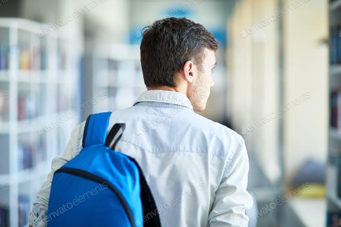 Pensive boy with satchel moving along corridor