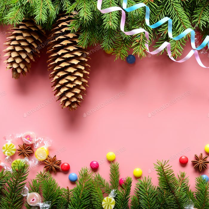 Flat lay design of Christmas greeting card of fir twigs cones, paper streamer, candies and spices