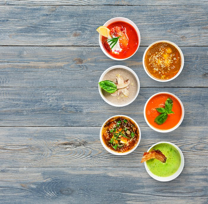 Six soups at blue wood, top view with copy space