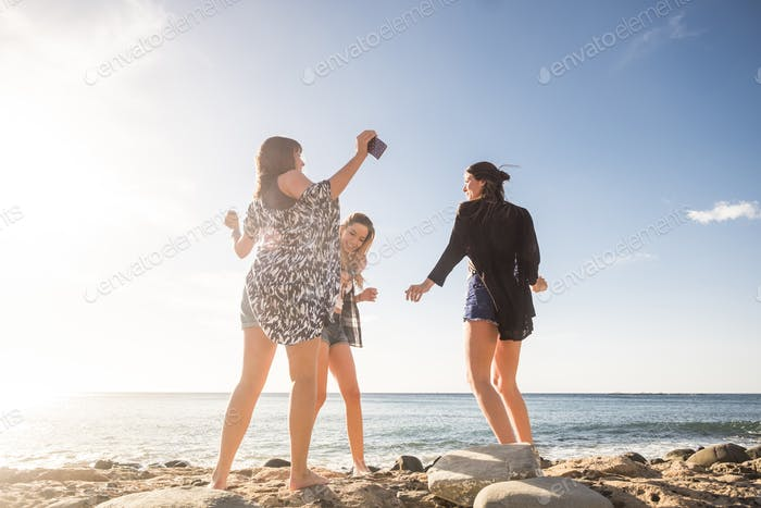 Group of young women friends enjoy and laugh having fun outdoor together - youthful