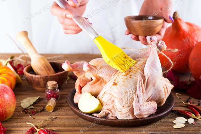 Women's hands smear sauce raw, fresh chicken on a wooden table. Step-by-step cooking
