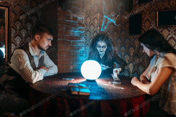 Hexe liest einen Zauberspruch über eine Kristallkugel