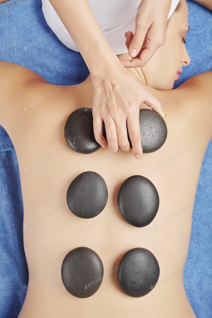Massage with heated rocks