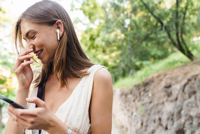 Image of young woman in earbuds laughing and holding cellphone in park
