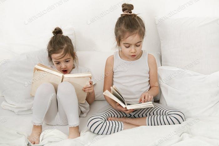 Dos hermanitas lindas niñas están leyendo un libro en la cama en el dormitorio.