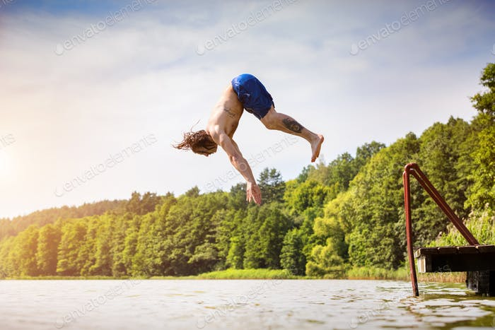 Young fit man jumping into a lake