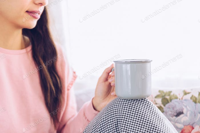 Young woman drinking coffee or tea sitting by the window