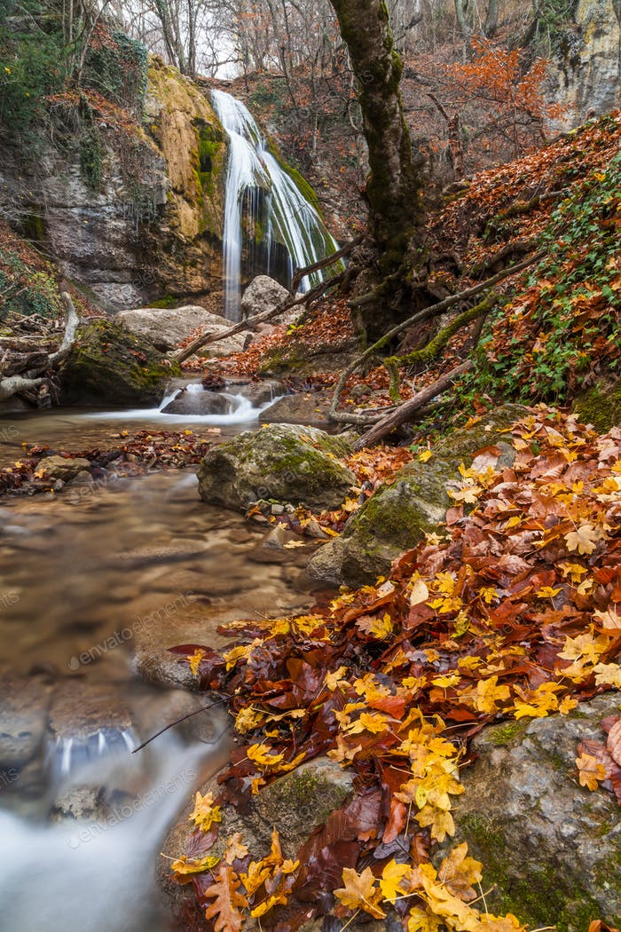 Beautiful autumn landscape with a waterfall in the autumn forest
