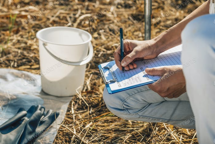 Soil Test. Female Agronomist Taking Notes In The Field