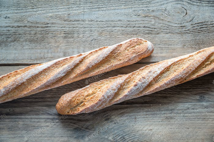 Two wholewheat baguettes on the wooden background