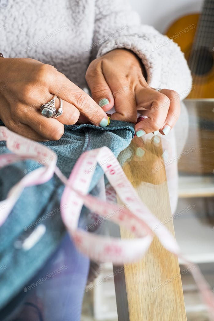 Close up of woman caucasian hands working like tailor at home - home work job activity