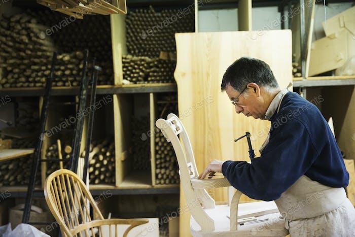 Mann arbeitet auf einem Holzstuhl Markierung der Armlehne Gelenk