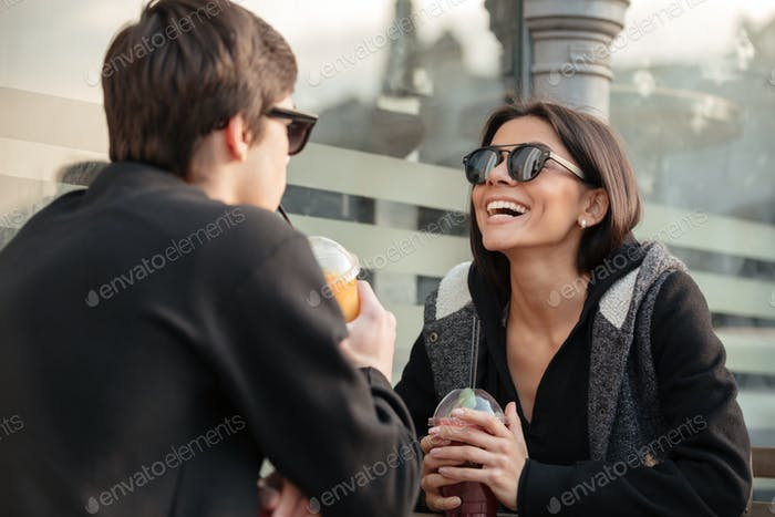 Laughing young lady sitting outdoors with her brother
