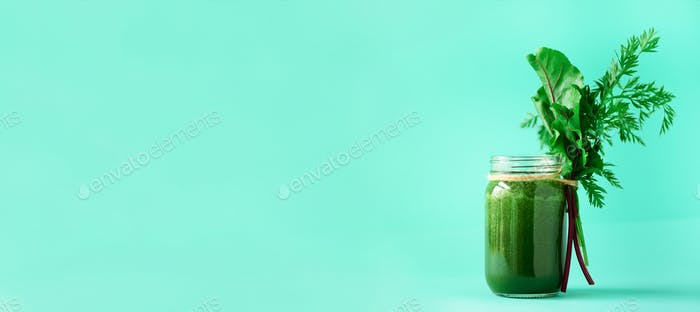 Banner of green smoothie with leafy beet greens and carrot tops on blue background, copy space