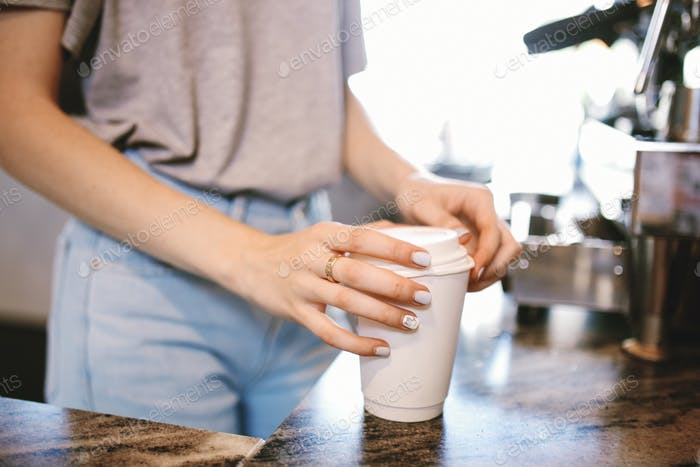 A slim young beautiful girl,dressed in casual outfit, gently puts the lid on the coffeein a cozy
