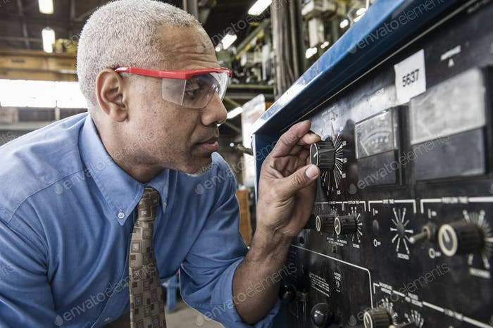 Black man factory owner checking gauges on a piece of welding equipment.