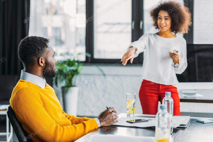 african american businesswoman pointing on colleague in office