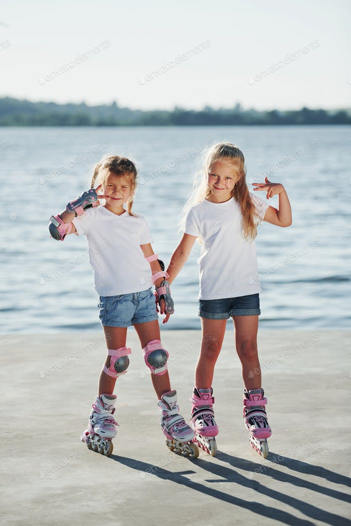 Posing for a camera. Happy female friends on roller skates. Leisure time