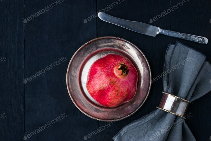 Pomegranate  on the vintage metal plate with knife and napkin horizontal