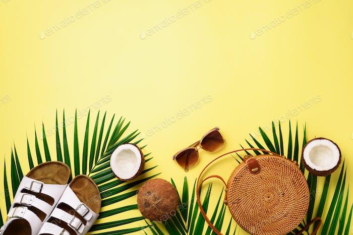Stylish rattan bag, coconut, birkenstocks, palm branches, sunglasses on yellow background. Banner