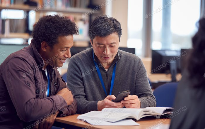 Teacher With Mature Male Adult Student Using Mobile Phone At Table Working In College Library