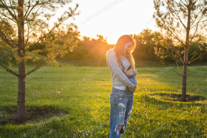 Pregnant girl outdoors on a sunset