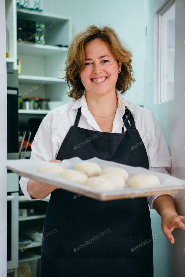 Smiling woman with raw buns on tray