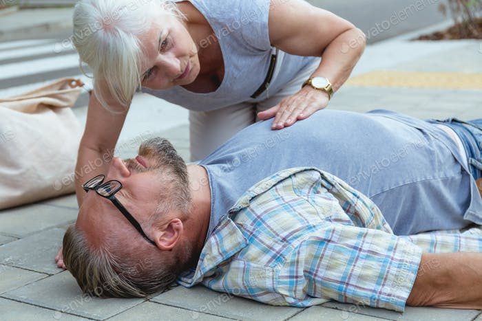 Helpful passerby checks the vital functions of the person who fainted on the street