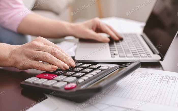 Senior woman with calculator counting dollar money at home