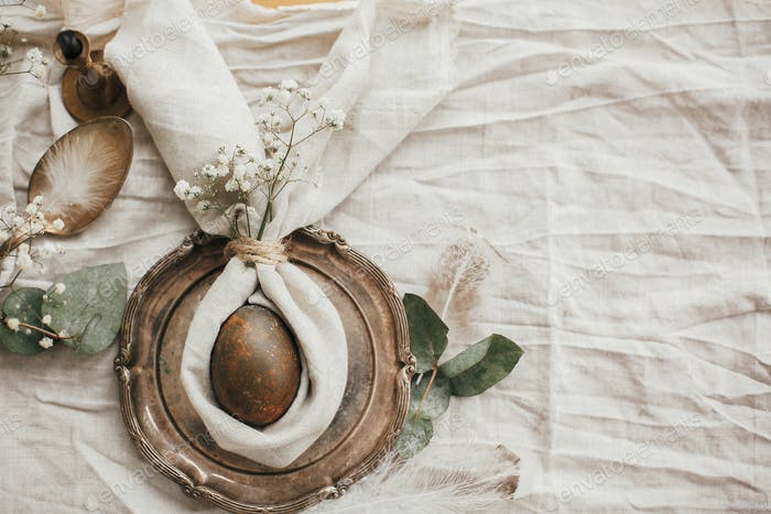 Modern natural dyed egg on napkin with bunny ears, flowers on vintage plate