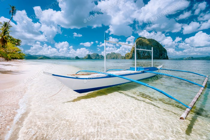 El Nido, Palawan, Philippines. Tropical scenery of banca boat on the sandy beach ready for island